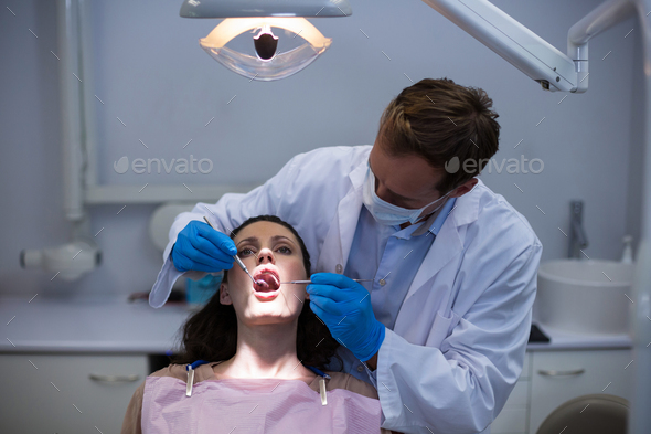 Dentist examining a female patient with tools - Stock Photo - Images