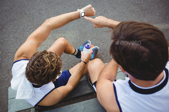 Overhead view of basketball players looking at smartwatch - Stock Photo - Images