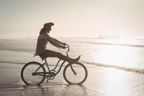 Side view of cheerful woman riding bicycle on shore at beach - Stock Photo - Images