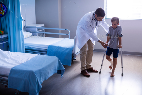 Doctor assisting injured boy to walk with crutches - Stock Photo - Images