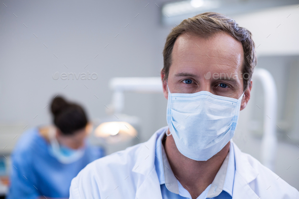 Dentist wearing surgical mask in dental clinic - Stock Photo - Images