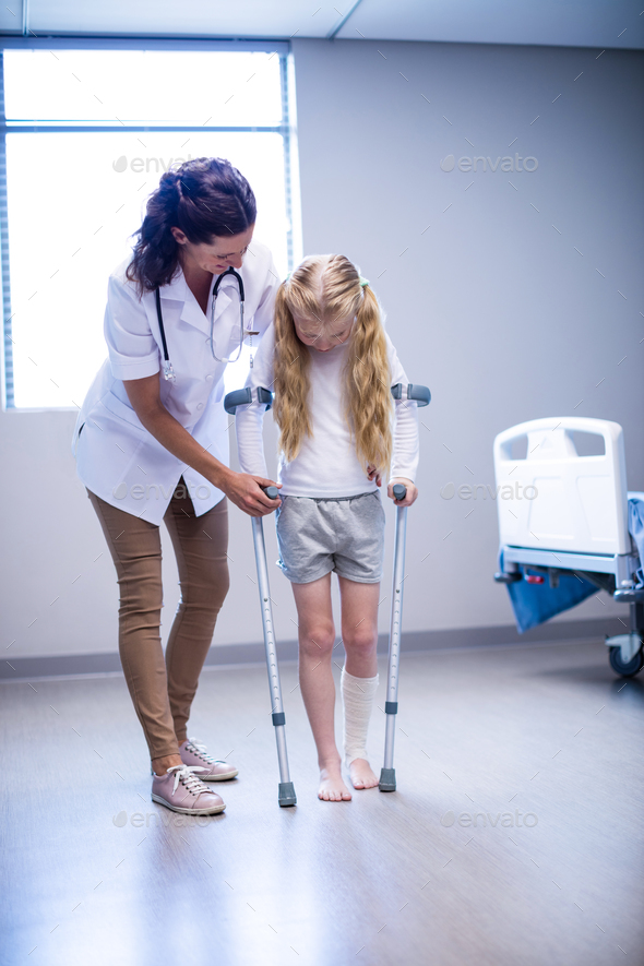 Female doctor assisting girl to walk with crutches in ward - Stock Photo - Images