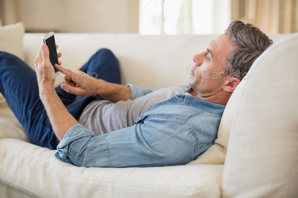 Man Lying On Sofa And Using Mobile