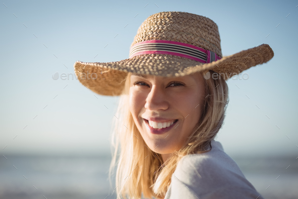 Portrait of happy woman wearing sun hat at beach - Stock Photo - Images