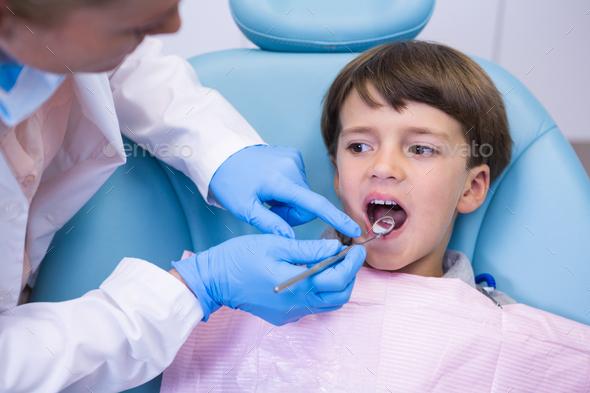 Dentist examining boy at clinic - Stock Photo - Images