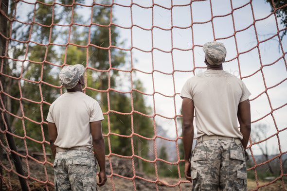 Military soldiers looking at net during obstacle course - Stock Photo - Images