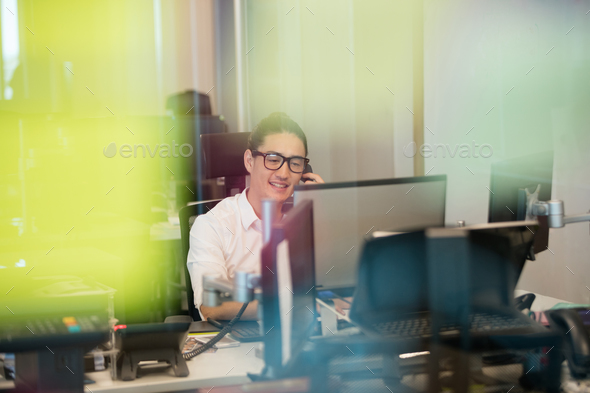Smiling business executive talking on phone at office - Stock Photo - Images