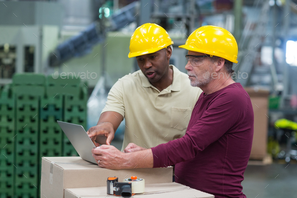 Factory workers discussing while working on laptop in drinks production plant - Stock Photo - Images