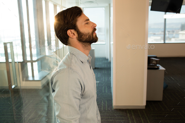 Side view of sad businessman leaning on glass - Stock Photo - Images