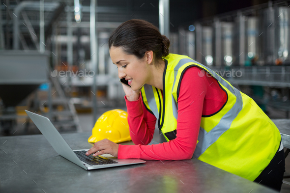 Female factory worker using laptop while talking on mobile phone - Stock Photo - Images