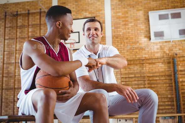 Basketball player doing fist bump with coach - Stock Photo - Images