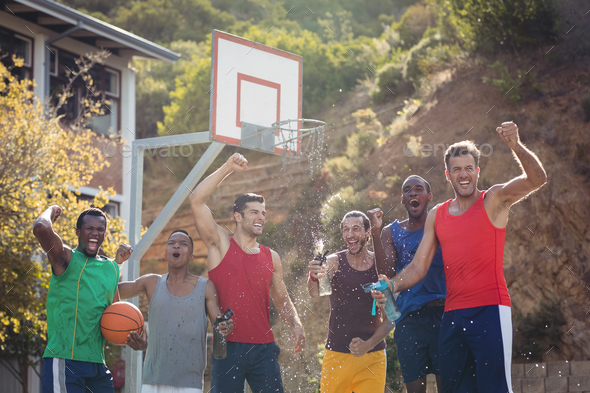 Basketball players celebrating by splashing water on each other - Stock Photo - Images