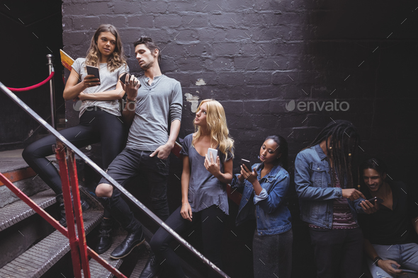 Young friends using mobile phone at nightclub staircase - Stock Photo - Images