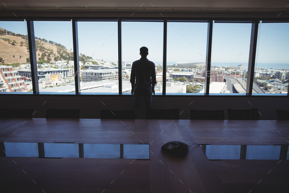 Male business executive looking through window - Stock Photo - Images