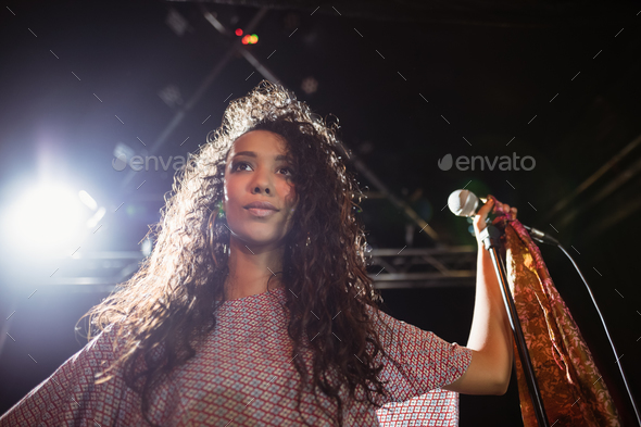Thougthful young female singer holding mic at nightclub - Stock Photo - Images
