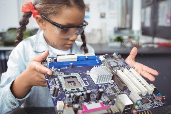 Elementary schoolgirl examining circuit board at electronics lab - Stock Photo - Images