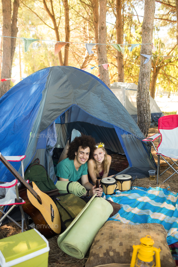 Portrait of smiling couple in tent - Stock Photo - Images