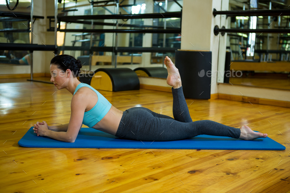 Beautiful woman performing stretching exercise - Stock Photo - Images