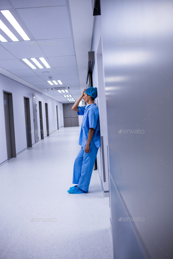 Sad surgeon leaning on wall in corridor - Stock Photo - Images