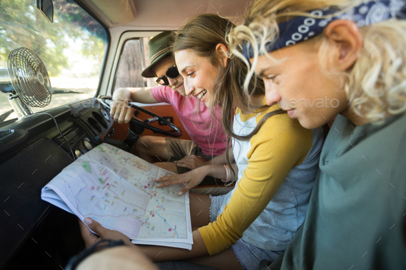Smiling friends reading map in camper van - Stock Photo - Images
