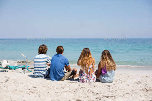 Rear view of friends sitting on during sunny day - Stock Photo - Images