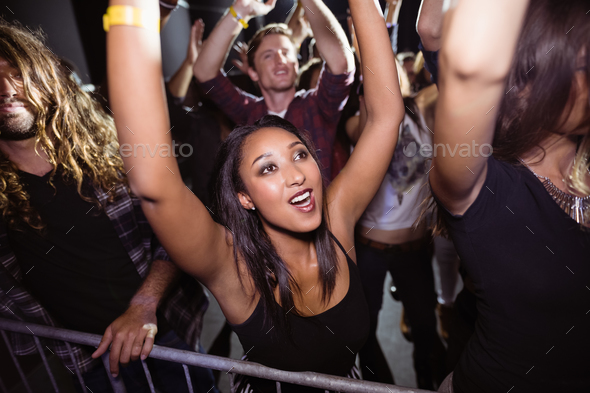 Woman with crowd enjoying at night - Stock Photo - Images