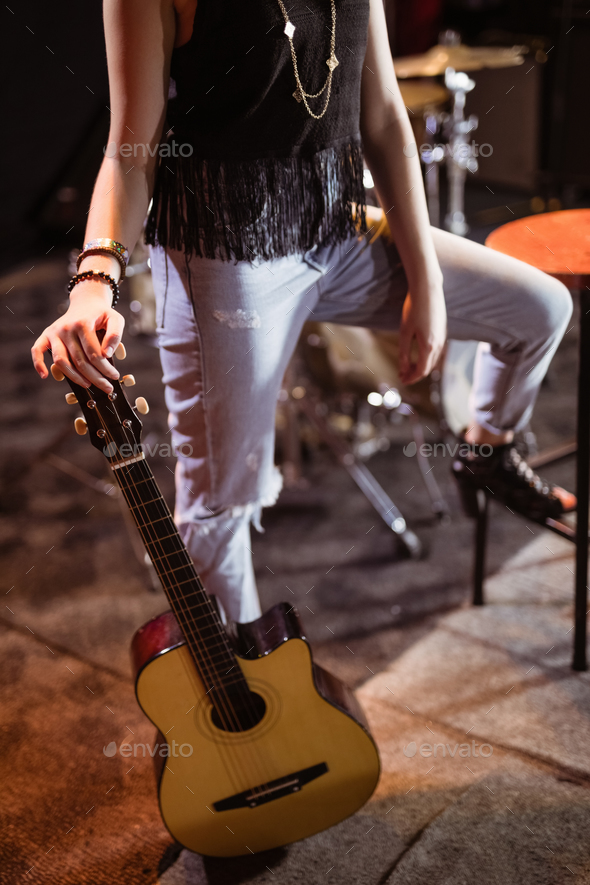 Low section of woman with guitar - Stock Photo - Images