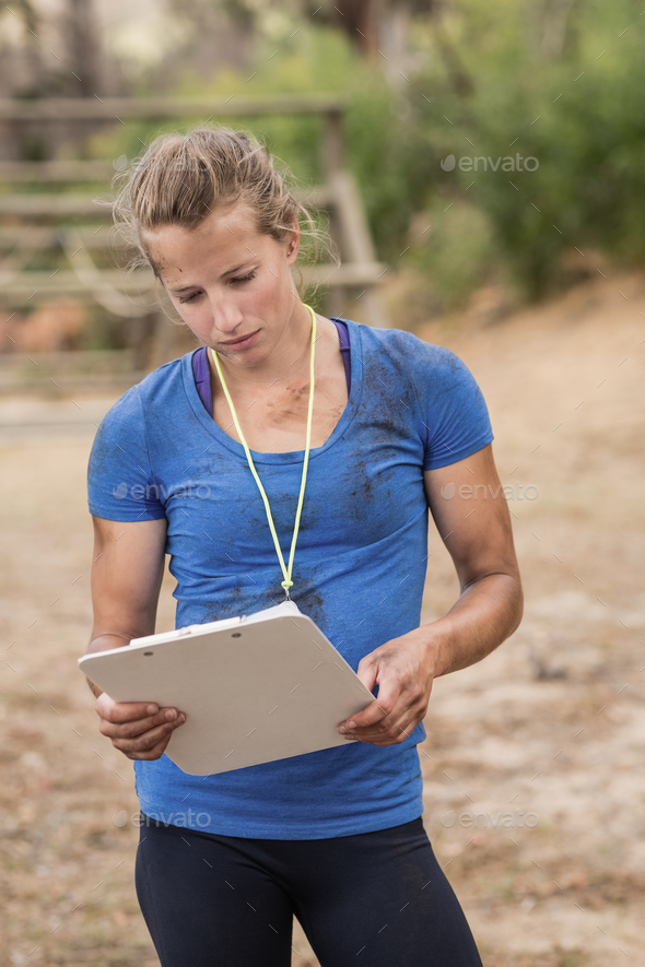 Female trainer holding clipboard during obstacle course - Stock Photo - Images