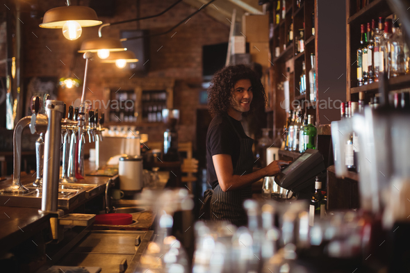 Young waiter using a electronic machine - Stock Photo - Images