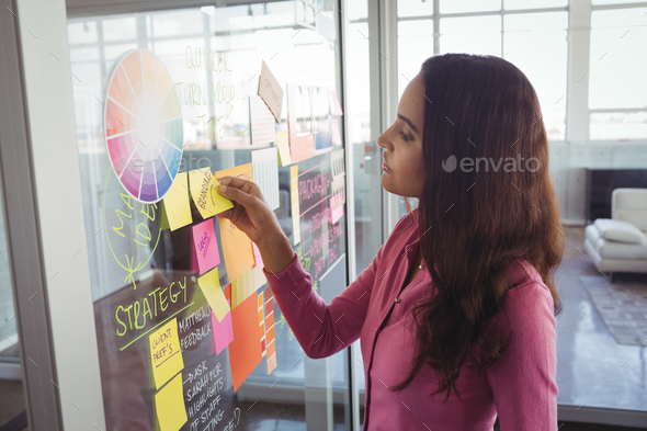 Female designer removing adhesive note from glass in creative office - Stock Photo - Images