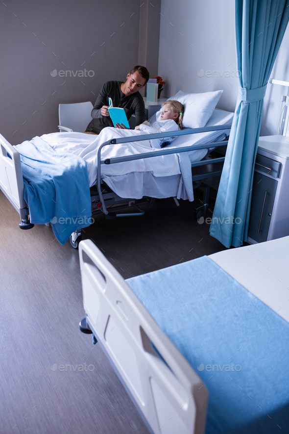 Girl on a hospital bed reading book with her father - Stock Photo - Images