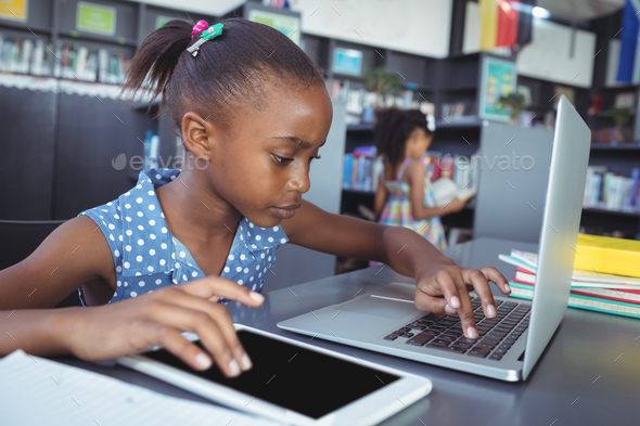 Girl using tablet computer and laptop in library - Stock Photo - Images