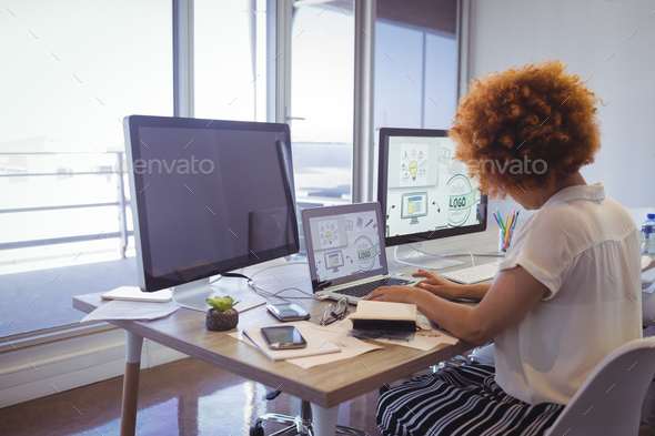 Focused businesswoman working in office - Stock Photo - Images