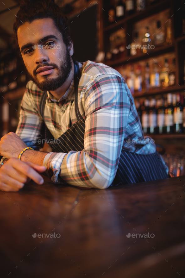 Portrait of waiter leaning at counter - Stock Photo - Images
