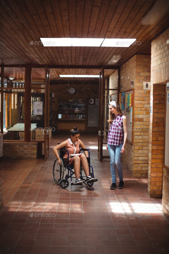 Schoolgirl talking with her disabled friend in corridor - Stock Photo - Images