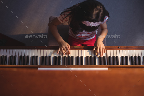 Overhead view of elementary girl playing piano in classroom - Stock Photo - Images