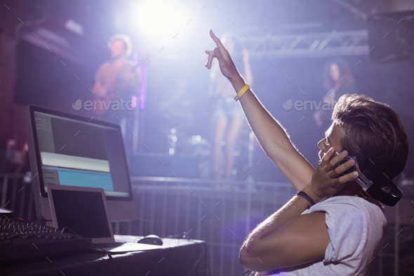 Young male dj with arms raised performing at nightclub - Stock Photo - Images
