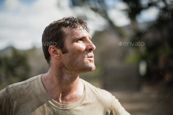 Military man standing during obstacle course - Stock Photo - Images