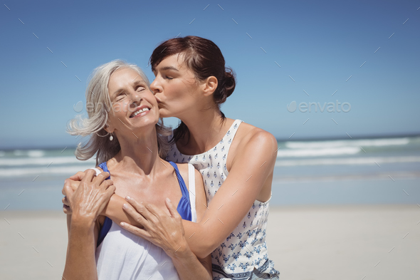 Young woman kissing her mother at beach - Stock Photo - Images