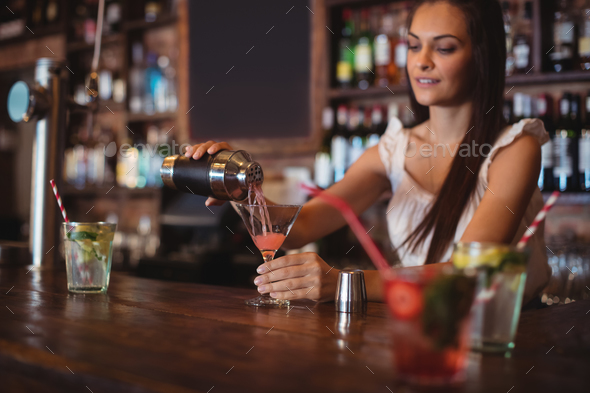 Female bartender pouring cocktail drink in the glass - Stock Photo - Images