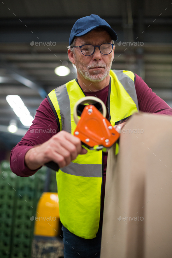 Factory worker sealing cardboard boxes - Stock Photo - Images