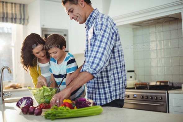 Parents and son preparing salad in the kitchen - Stock Photo - Images