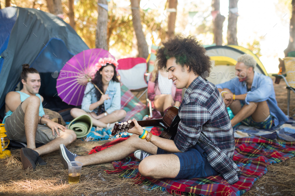 Young man playing guitar while sitting with friends at campsite - Stock Photo - Images