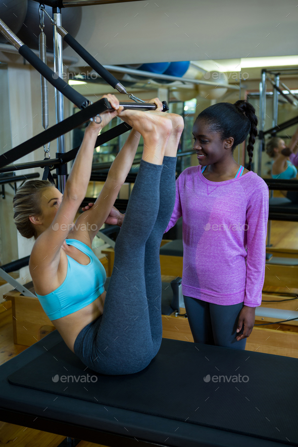 Smiling trainer assisting woman with pilates on reformer - Stock Photo - Images