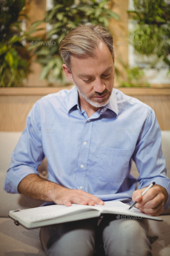Attentive doctor writing in organizer - Stock Photo - Images