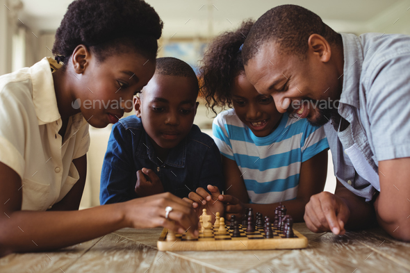 Family playing chess together at home in the living room - Stock Photo - Images