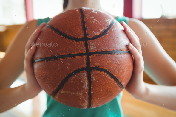 Midsection of female basketball player holding ball - Stock Photo - Images