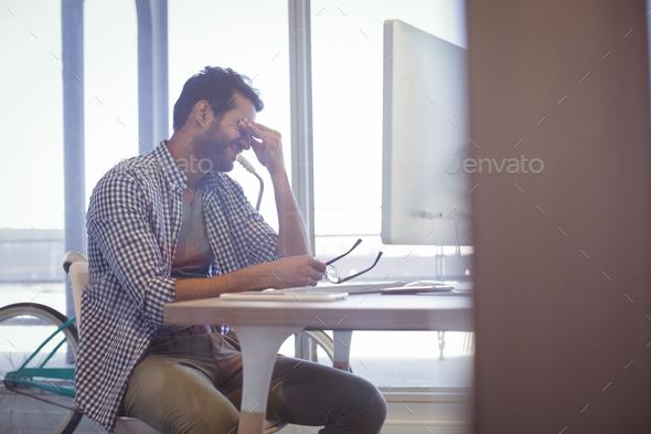 Depressed businessman sitting at desk - Stock Photo - Images