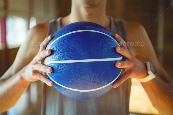 Midsection of basketball player holding ball - Stock Photo - Images