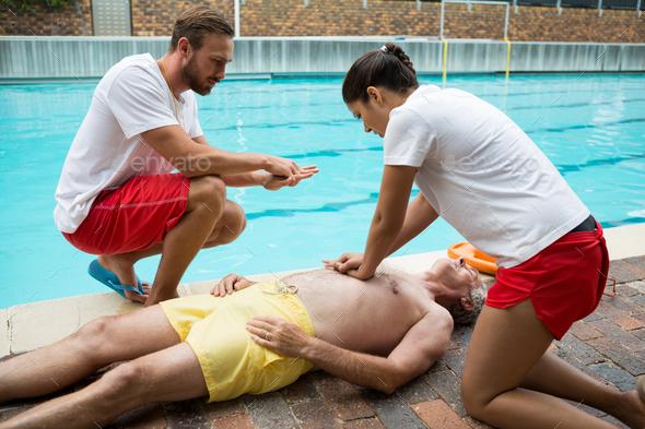 Lifeguards pressing chest of unconscious senior man - Stock Photo - Images